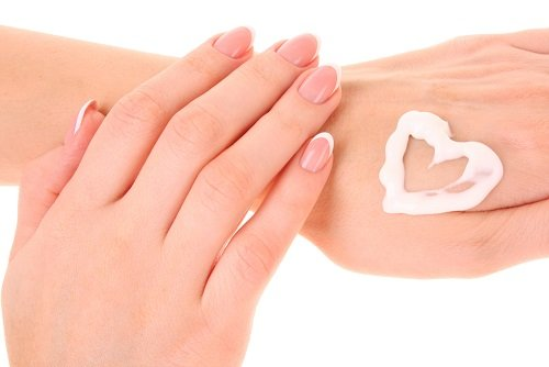 Two woman hands spreading the cream in the form oh heart isolated on white